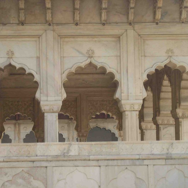 Cusped arches and arabesque floral patterns carved in white marble.