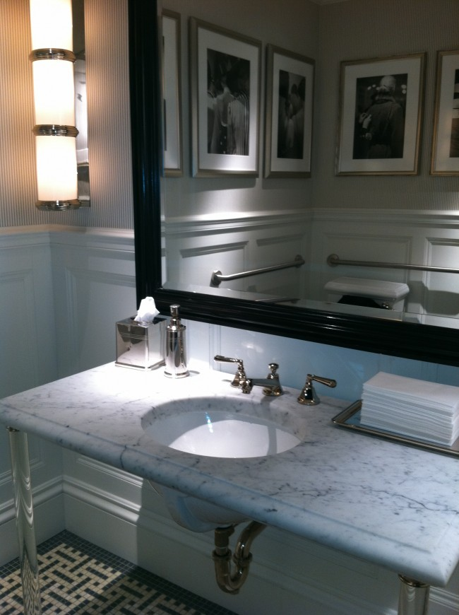 The ladies room in the new Ralph Lauren women's store on Madison Avenue and 79th Street is signature RL. The use of a Cararra marble counter top on washstand legs, a mosaic floor and beautiful black and white photographs is always classic.