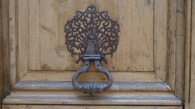 Similar to another knob, but this one appears to be made of iron.  It is prominent against the unpainted door.