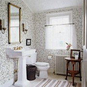 A well blended black and white bath with dainty wallpaper and a black and white striped rug to tie the space together.