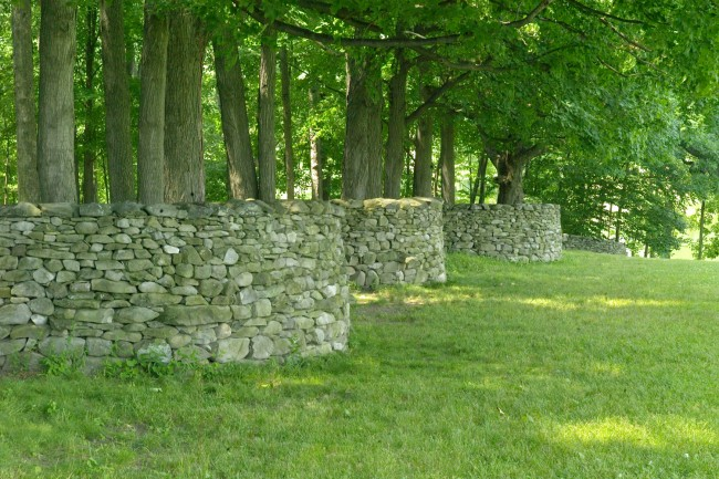 An exquisite undulating wall by Andy Goldsworthy gently folds around stands of old trees. The placement of the rocks on the top row is an artful finishing detail.