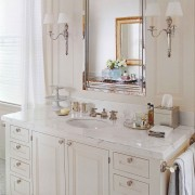 A simple vanity with bracket feet is beautifully accessorized with personal objects neatly collected on a tray.