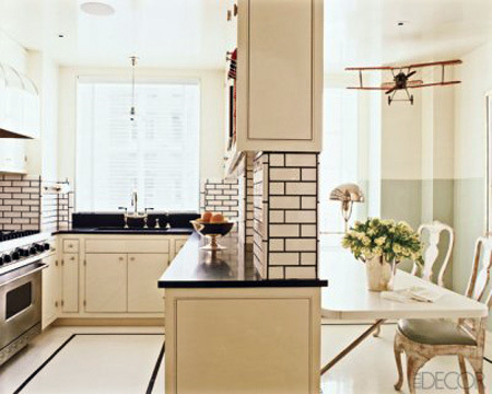 Dark grout on white tiles ties into the black counter top and border in the floor. This large grout joint and black grout adds a graphic element to this space.