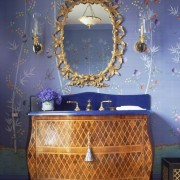 A bombe inlaid chest adapted as a vanity. Between the decorative mirror, the blue counter and wallpaper, this is a very stylized space.