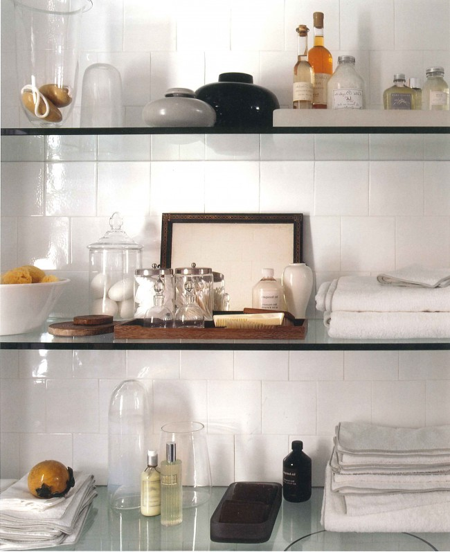 An oversized niche with thick glass shelves across from the vanity looks like a magnified medicine cabinet. Beautiful detail, gleaming white tile and practical as well.