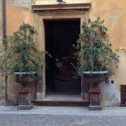 Doorways of all kinds host lovely knockers to announce visitors. This charming and welcoming doorway is in Bologna.