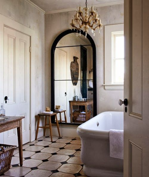 Another version of rustic is country house informal. The space is traditional, the floor limestone with cabochon and the tub is a reproduction of an early 20th century model. This is somewhere between charming country and rustic.