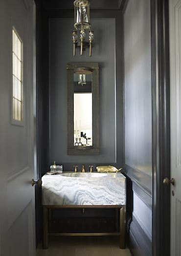 Dark gray walls and a beautiful stone sink give this very narrow powder bath a great presence. The tall thin mirror accentuates the scale of the space.