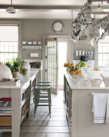 A nearly all gray kitchen relieved by the white Cararra counter tops, the massive rack of stainless cookware and the dark metal stools.  The natural light adds warmth to the space.