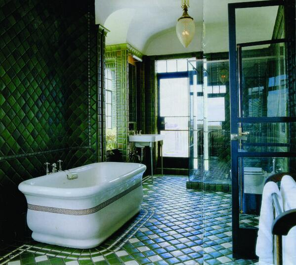 A lovely open space with extraordinary ceramic tile details. A rich palette of shaded green and vintage details combine to make this a memorable bath.
