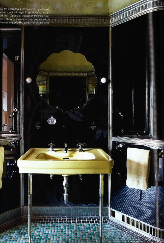Yellow is not the color of choice for contemporary baths, but is is perfect in this Art Deco setting against  black glass walls. A beautiful scalloped mirror hangs over the sink and simple globe sconces are on either side of it.