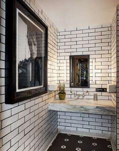 I love white tile with dark grout and the use of art in a public bathroom.