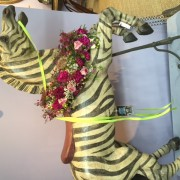 A colorful carousel horse decked out with flowers.