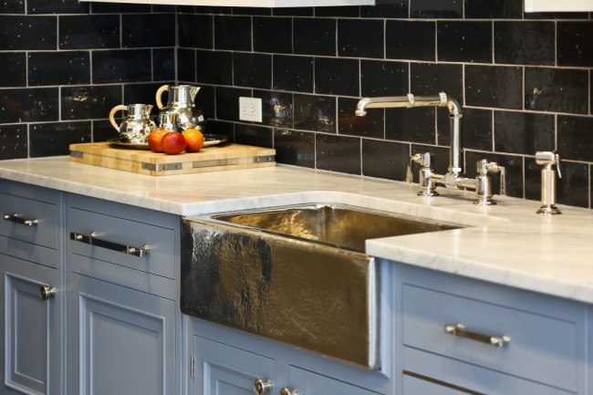 A dark and textured backsplash, a fabulous wood cutting board and pewter accessories collected in one place make a great statement.